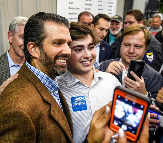 Donald Trump Jr., left, poses for a photo  after speaking at the Good Ole Boys & Gals barbecue in Oxford, Miss. The Trump Organization's decision to explore a sale of its Washington hotel stems from concern over claims of conflicts of interest related to international guests, according to Donald Trump Jr.