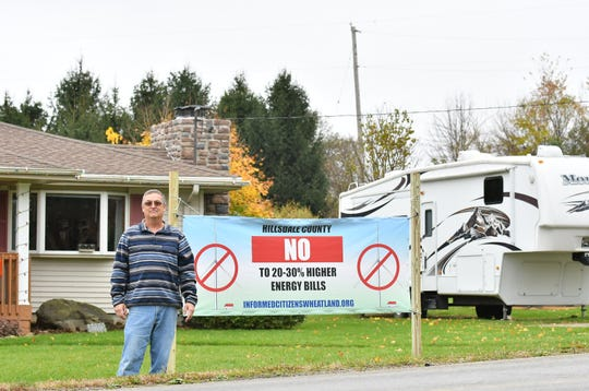 Chris Pollard, 58, with a banner in front of his home in Wheatland Township, Mich. on Oct. 29, 2019.  Pollard is the founder of the local anti-wind development group, Informed Citizens of Wheatland Township, and does not want a 500 foot tall wind turbine behind his home.  The turbine would be located beyond the electrical pole at the center of the photo.