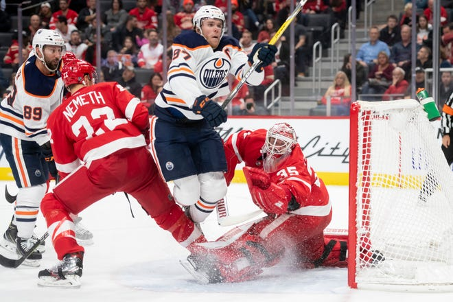 Edmonton center Connor McDavid flies between Detroit defenseman Patrik Nemeth, left, and goaltender Jimmy Howard while trying to score during the second period.