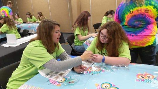 STEM teacher Jennifer Church works with Aubrey Martin, 12, of Fremont Middle School on a tooth brush robot.