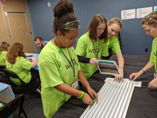 Leila Williams, 13, of Tiffin, practices with her tooth brush robot before a race at Whirlpool Tuesday.