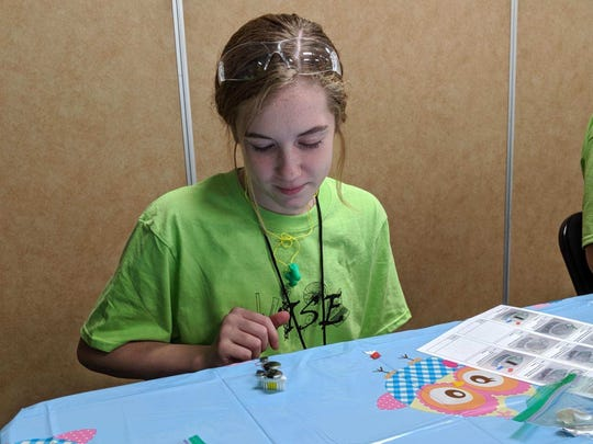 Danica Denman works on her tooth brush robot she used to win races during the Women in Science and Engineering event at Clyde Tuesday.