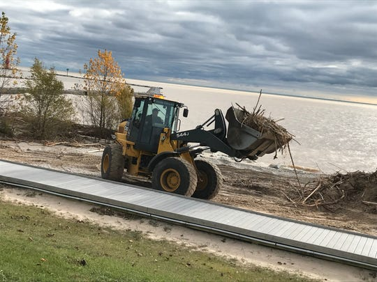 A front loader hauls a pile of debris from Crescent Beach in Algoma on Oct. 23, where waves from unusually strong east-southeasterly winds winds off Lake Michigan threw driftwood, old tires and more onto the shore.