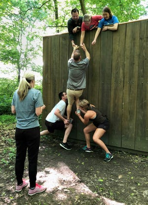 Henderson Leadership Initiative class members Quinn Thomas and Lindsay Locasto prepare to push up classmate Joe McGarrh by his feet while Wes Alexander, Tara Dixon and Allison Hancock stand ready to pull him over a wall during an exercise at the Brain Injury Adventure Camp last May. Kelsey Hargis stands by, awaiting her turn. The exercise was one of several designed to provide class members an opportunity to brainstorm and show teamwork while also helping them bond.