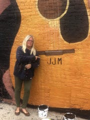 "Pamela Bliss points to the initials, ""JJM,"" John Mellencamp added to her mural Tuesday afternoon."