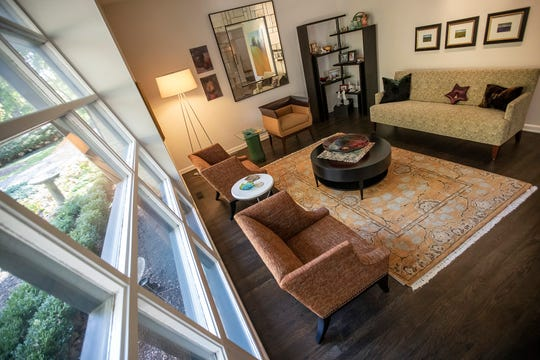 A living room, featuring a large slanted mid-century style window, at 7020 North Delaware Street on the north side of Indianapolis, which was on the market for $699,900, seen on Wednesday, Oct. 23, 2019. The Arden home has three bedrooms, two full bathrooms and two half bathrooms.