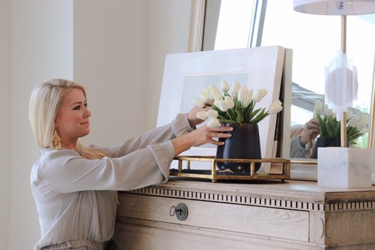 Kayce Saik arranges flowers in the new showroom of Relish, an interior design business.