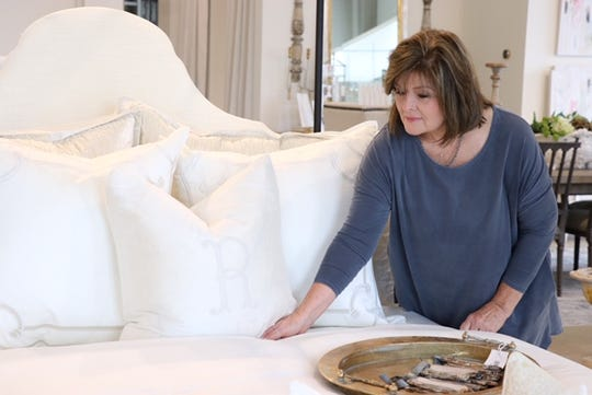 Kathy Cotten fluffs a bedding display at the new showroom of Relish in the Gluckstadt area of Madison.