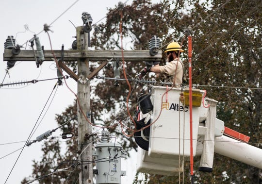A lineman fixes power lines in a neighborhood in Adamsville, Tenn., Monday, Oct. 28, 2019 after a storm knocked out power in large parts of McNairy, Hardin and Decatur counties. More than a dozen crews from outside the damaged areas have helped with power restoration efforts since Sunday.