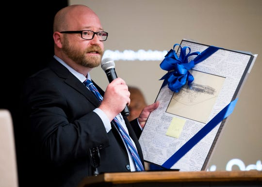Newly appointed Knox County Public Defender Eric Lutton holds a gift for Mark Stephens during a dedication ceremony at the newly renamed Mark Stephens Community Law Office in Knoxville on Wednesday, October 30, 2019.