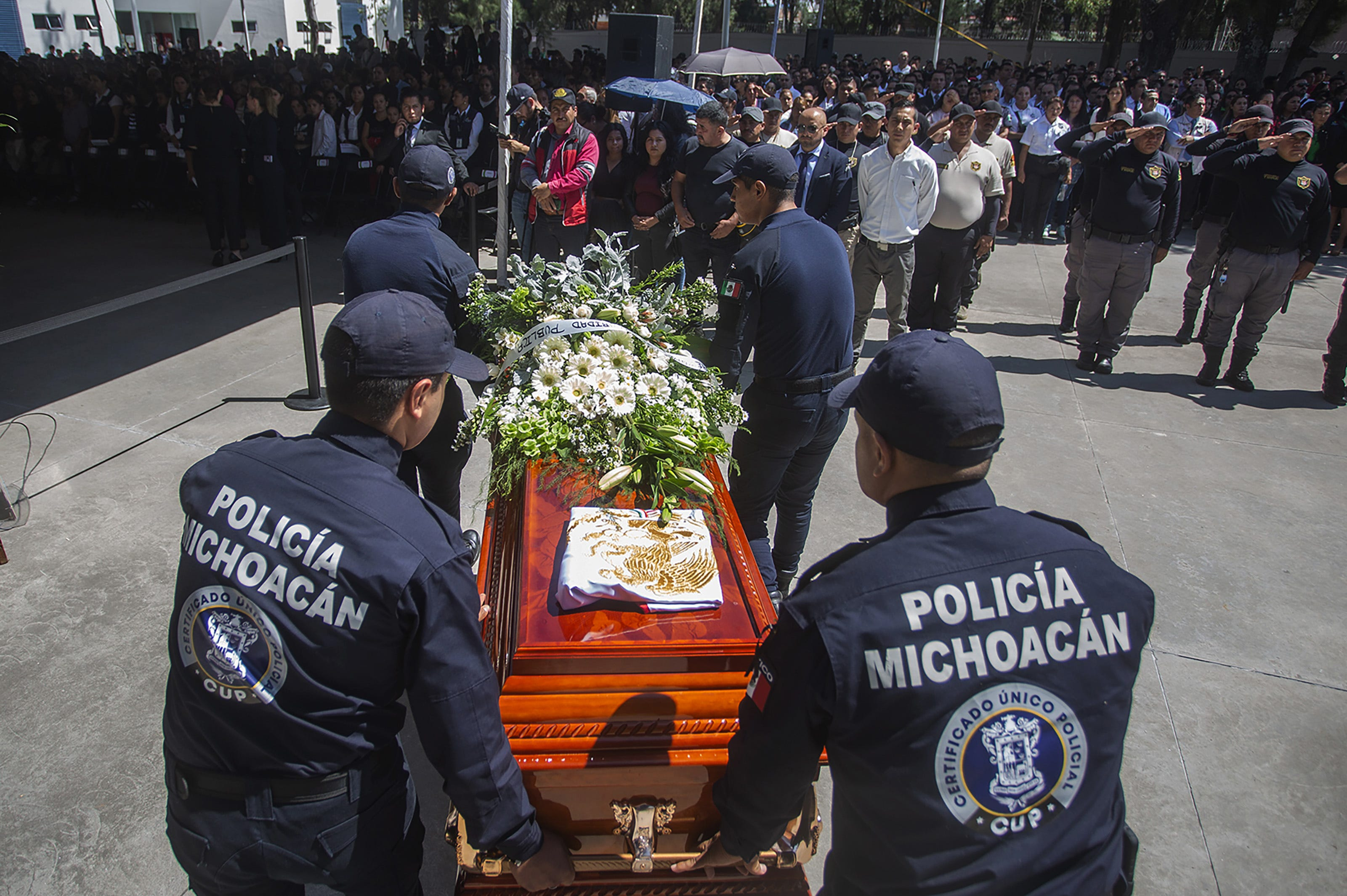 Relatives and members of the Michoacán police department pay tribute to 13 officers killed in an ambush on Oct. 14, 2019.