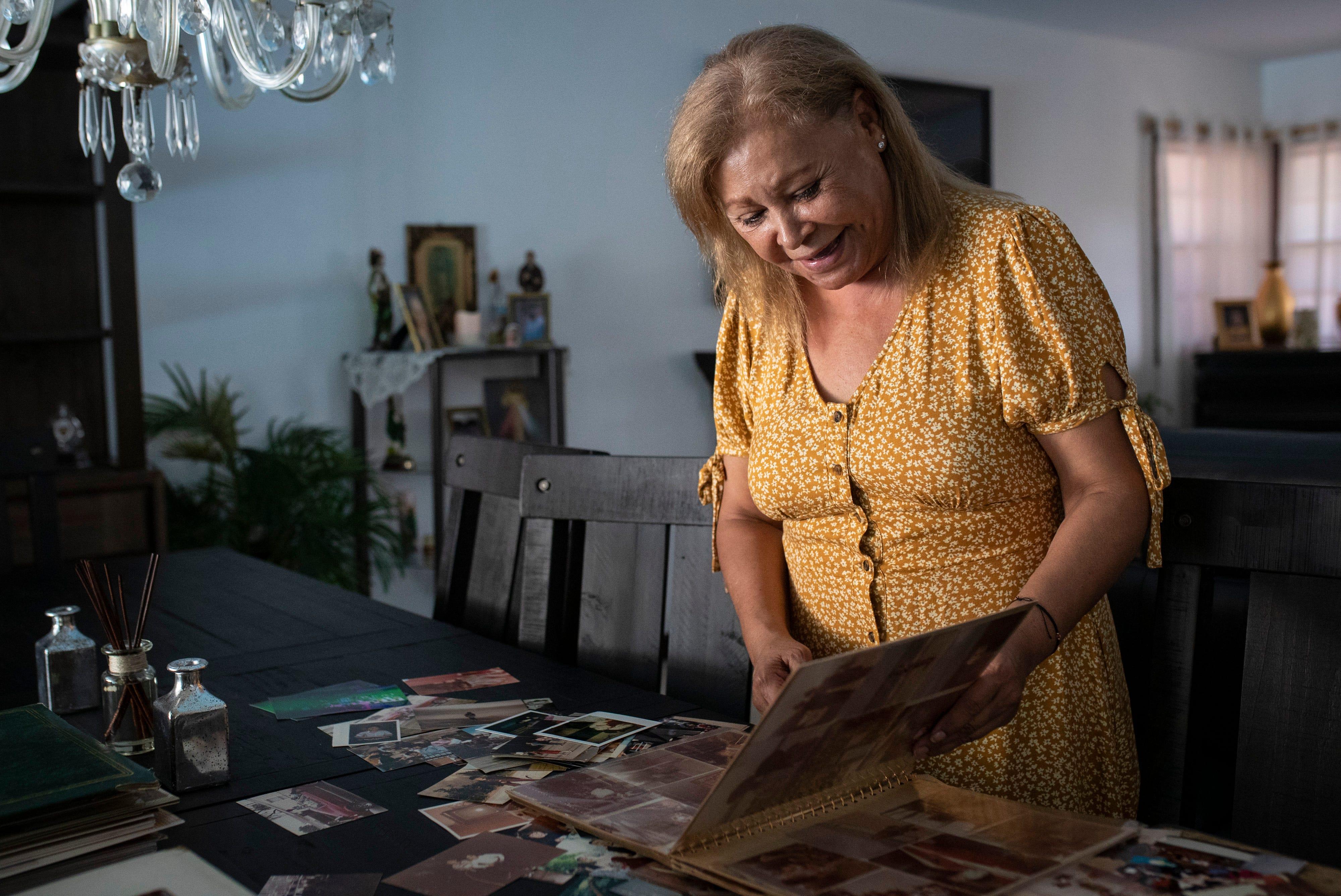 Carmen Macias, 62, looks through family photographs of her son Oscar Macias, who disappeared in 2014.