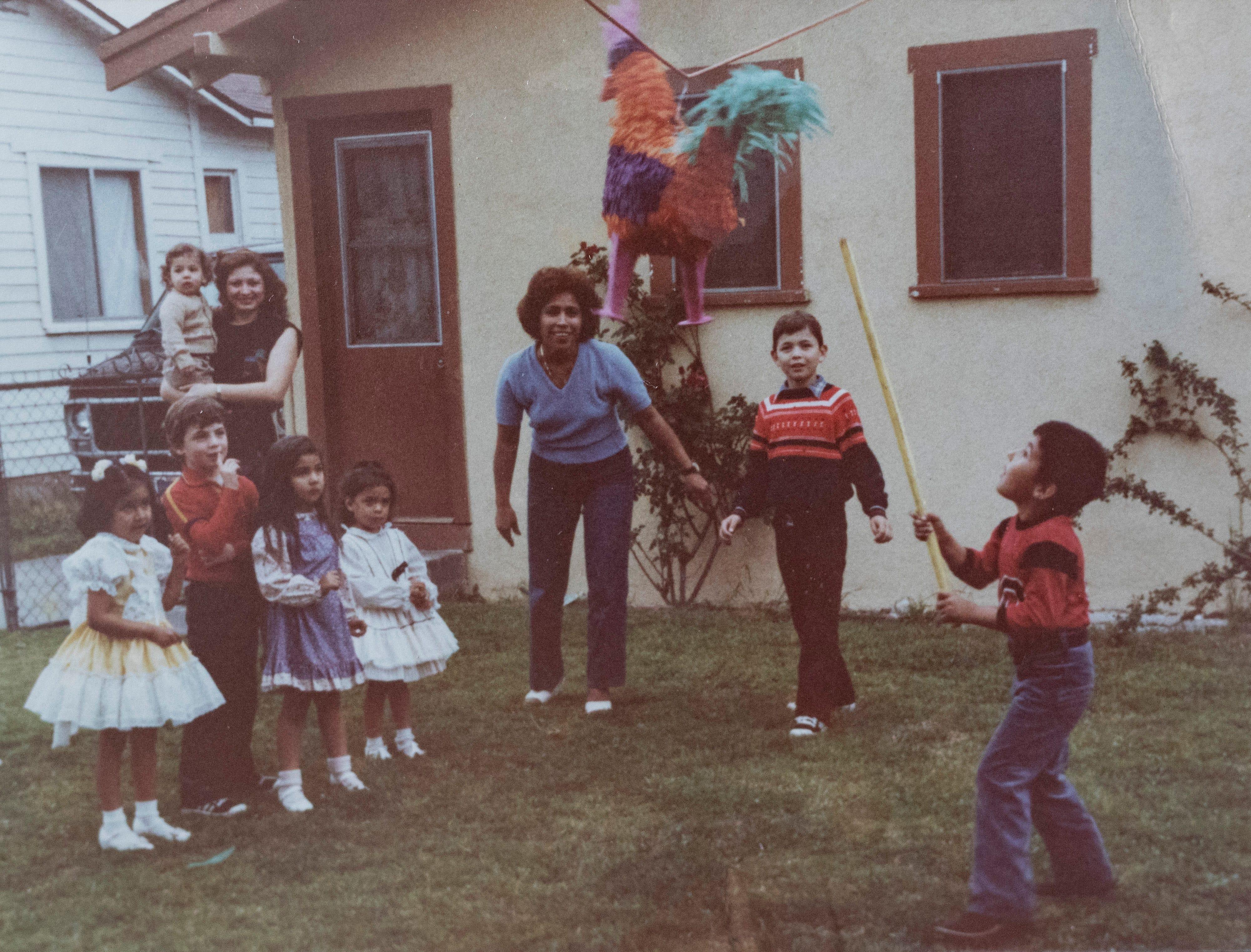 Oscar Macias attempts to bust a piñata in a family photograph.