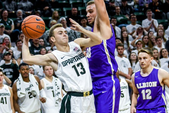 Michigan State's Steven Izzo, left, is fouled by Albion's Alex Warman during the second half on Tuesday, Oct. 29, 2019, at the Breslin Center in East Lansing.