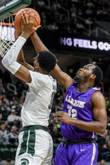 Former Holt High School Ram and Albion forward Quinton Armstrong, right, blocks a shot by Marcus Bingham Jr. during the first half on Tuesday, Oct. 29, 2019, at the Breslin Center in East Lansing.