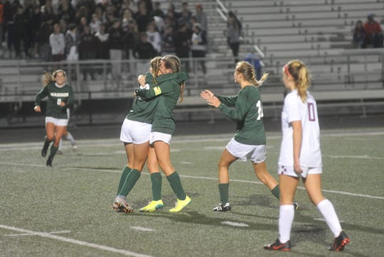 Madison's Taylor Huff hugs Kalie Blaising after her the two linked up for the second goal.