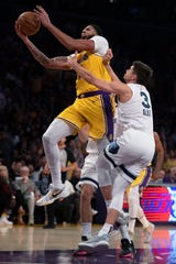Los Angeles Lakers forward Anthony Davis, left, leaps for a basket next to Memphis Grizzlies guard Grayson Allen during the second half of an NBA basketball game in Los Angeles, Tuesday, Oct. 29, 2019.