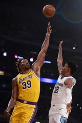 Memphis Grizzlies guard Ja Morant, right, shoots a floater over Los Angeles Lakers center Dwight Howard during the first half of an NBA basketball game in Los Angeles, Tuesday, Oct. 29, 2019. (AP Photo/Kyusung Gong)