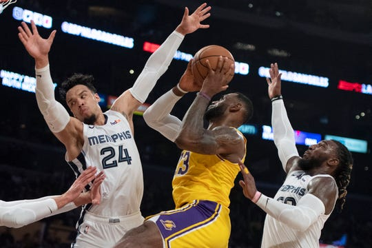 Los Angeles Lakers forward LeBron James, center, looks to shoot under pressure from Memphis Grizzlies guard Dillon Brooks, left, and forward Jae Crowder during the second half of an NBA basketball game in Los Angeles, Tuesday, Oct. 29, 2019.
