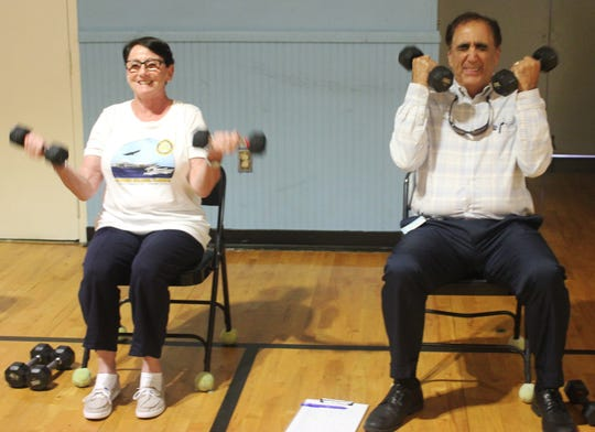 Rotarians Patricia Rutledge and George Abounader exhibit different emotions as they do the weights session.
