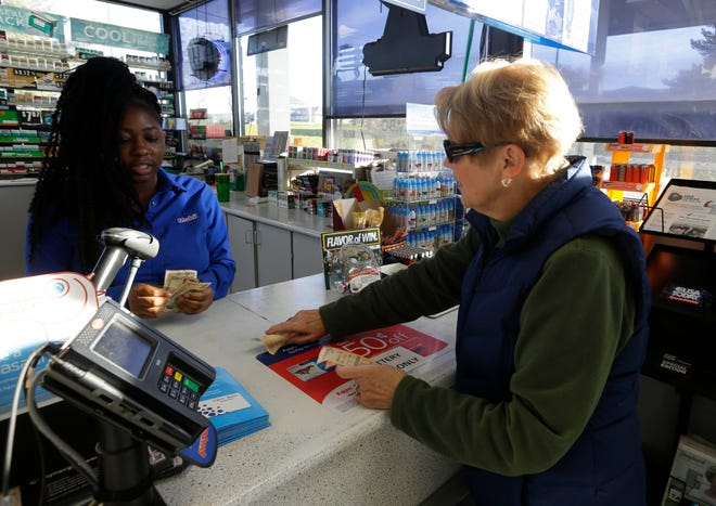 Julie Egan of the Town of Brookfield buys lottery tickets at Pewaukee Corner Pump last year when the Mega Millions jackpot was about $1.6 billion, the largest jackpot in U.S. history.