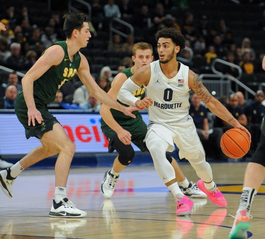 Marquette guard Markus Howard looks for space in the lane around St. Norbert guard Jack Pettit on Tuesday.