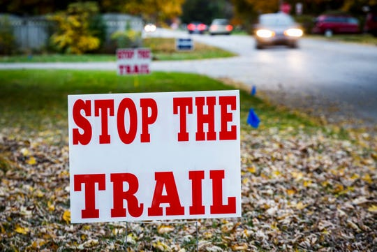 Signs opposing a proposed trail posted by homeowners line a section of Riverside Avenue west of Tillotson Avenue Tuesday afternoon.