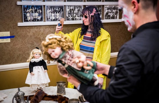 Claire Enk, dressed as Coraline, helps set up the evil doll room at the Ball Honors House.