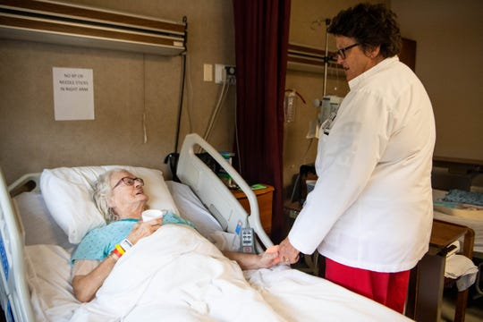"Betty Harvey, 83, left, holds hands with nurse Nancy Daniel while recovering from pneumonia at Three Rivers Hospital on Oct. 29, 2019. The hospital is at risk of closure, but Harvey calls it ""home."""