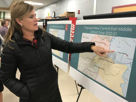 Mother of four Stephanie Rainey reviews the rezoning proposal for the new central east middle school on Henpeck Lane.