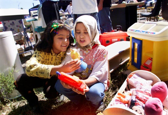 Safaa Al Huchimi, 9, left, and her sister, Shefa, 10, look over toys at Catholic Charities' warehouse as part of Hands on Nashville Day Oct. 2, 1999. The Al Huchimi's just arrived from Iraq on Sept. 29. Refugees claimed clothes and furniture at the warehouse, worked by numerous volunteers, many from Nortel Networks.