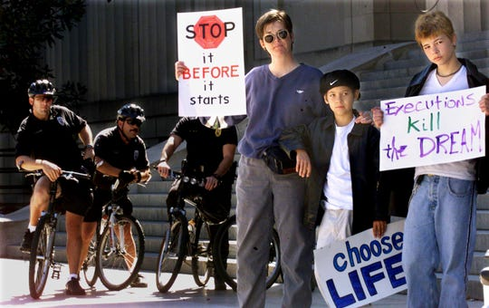 With Metro police watching nearby, the Rev. Jodie McCullah, left, and her sons, Spencer Hall and Arlo Hall to the rally at Legislative Plaza to speak out publicly against the death penalty Oct. 14, 1999.