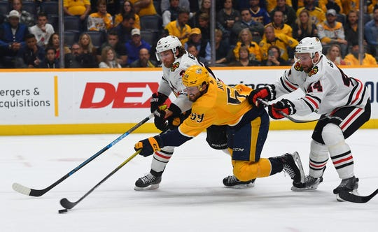 Nashville Predators defenseman Roman Josi (59) is hit by Chicago Blackhawks defenseman Duncan Keith (2) and defenseman Calvin de Haan (44) as he skates toward the net during the third period at Bridgestone Arena on Tuesday.