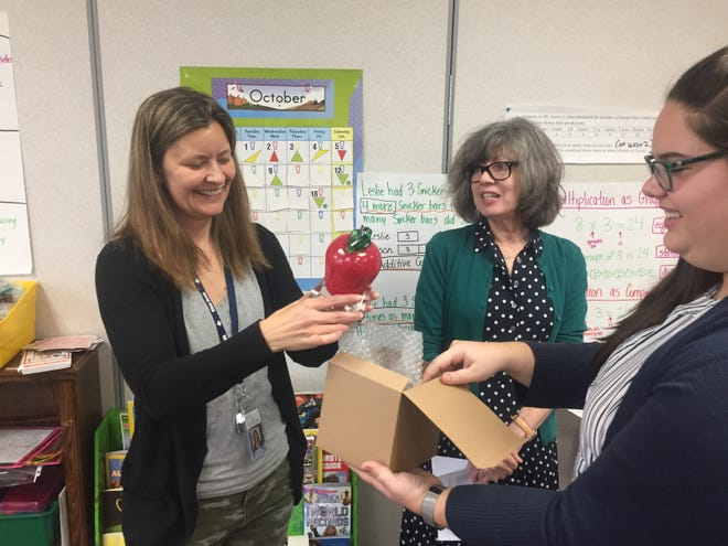 Granville Intermediate School instructor Jennifer McCollister (left) was surprised in her classroom by the Licking County Foundation's Connie Hawk and Alexia Rose on Oct. 29.