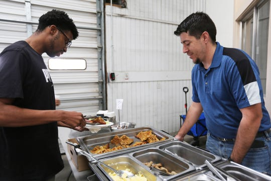 """Russell Hernandez, right, owner and CEO of Salud de Mesilla, serves """"Death in Texas"""" crew member Larry Jackson, of El Paso, before filming begins at the Film Las Cruces studios on Wednesday, Oct. 30, 2019."""