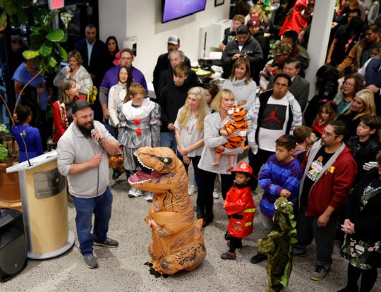 Sean Dugan, left, addresses the crowd at the Sherman Dugan Museum of Geology on Oct. 29, 2019, before the institution's new dinosaur display is unveiled.