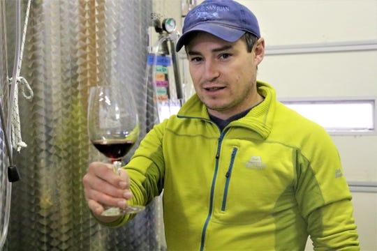 Joshua Arnold, head winemaker at Wines of the San Juan,  holds out a batch of still-processing wine at Wines of the San Juan in Blanco on Oct. 18, 2019.