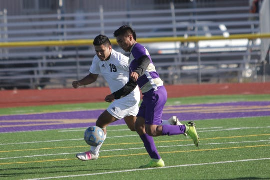 Aztec's Malakai Garcia and Kirtland Central's Anesio Villegas chase after the ball during a District 1-4A boys soccer match on Thursday, Oct. 24 at Bill Cawood Field in Kirtland.