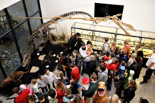 Visitors to the Sherman Dugan Museum of Geology at San Juan College check out the institution's new dinosaur exhibition during its unveiling ceremony on Oct. 29, 2019, in Farmington.