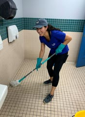 No job too small: Brie Holguin gets busy with mopping duties.