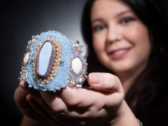 Pensacola artist Crystal King shows off some of her hand-made jewelry during a visit to the Pensacola News Journal on Oct. 22, 2019.  King is one of two artists selected by the Great Gulfcoast Arts Festival to have their work shown as an Emerging Artist.