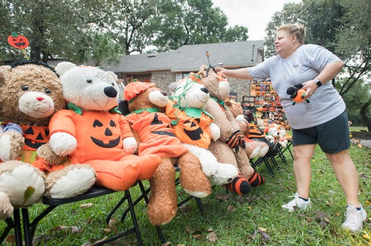 Teresa Nelson makes adjustments to her massive pumpkin display in front of her house on Meadow Brook Drive in Pensacola on Wednesday, Oct. 30, 2019.