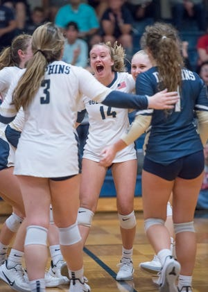 The Dolphins celebrate a winning a point during the Wakulla vs. Gulf Breeze playoff volleyball match at Gulf Breeze High School on Tuesday, Oct. 29, 2019.