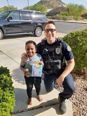 Officer Valdez of the Mesa Police Department poses for a photo with 5-year-old Charlie, who called 911 Sunday to order a Happy Meal, the agency said.