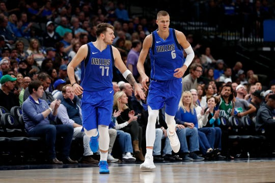 Dallas Mavericks' Luka Doncic (77) and Kristaps Porzingis (6) celebrate a basket against Portland Trail Blazers during an NBA basketball game in Dallas, Sunday, Oct. 27, 2019. (AP Photo/Tony Gutierrez)