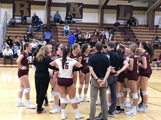 The Arlington High School volleyball team huddles during a timeout on Wednesday.