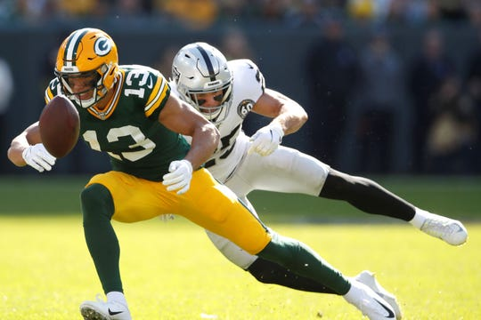 Green Bay Packers wide receiver Allen Lazard (13) drops a pass with coverage by Oakland Raiders free safety Erik Harris (25) during an NFL football game Sunday, Oct. 20, 2019, in Green Bay, Wis. The Packers won the game 42-24.