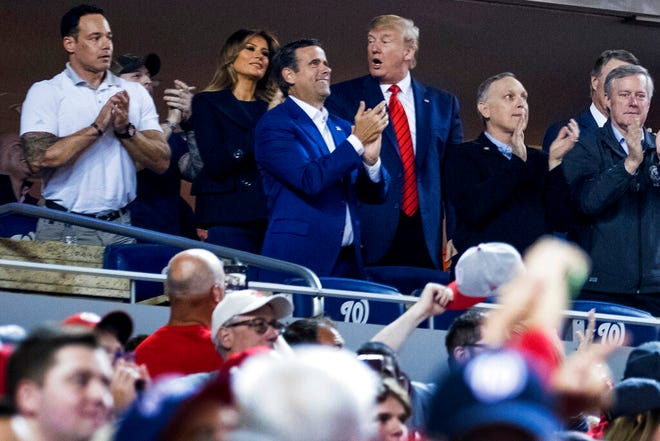 President Donald Trump, third from right, accompanied by first lady Melania Trump, second from left, and Republican lawmakers, reacts as the stadium boos when he is shown on the jumbo screen during a Salute to the Military during Game 5 of a baseball World Series game between the Houston Astros and the Washington Nationals at Nationals Park in Washington, Sunday, Oct. 27, 2019. Also Pictured are Rep. John Ratcliffe, R-Texas, center, and Rep. Mark Meadows, R-N.C., right. (AP Photo/Andrew Harnik)