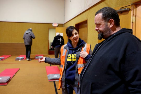 Ray Martin, 51, is helped by Lindsay Bigelow, a volunteer, at the warming shelter at South Salem Friends Church on Oct. 29, 2019, the first night this season with overnight temperatures that were expected to drop below 32 degrees.