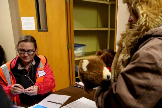 Jennie Banuelos, left, a volunteer, checks in Danielle Ceballos, 39, to the warming shelter at South Salem Friends Church on Oct. 29, 2019. Tuesday night was the first night this season with overnight temperatures expected to drop below 32 degrees.